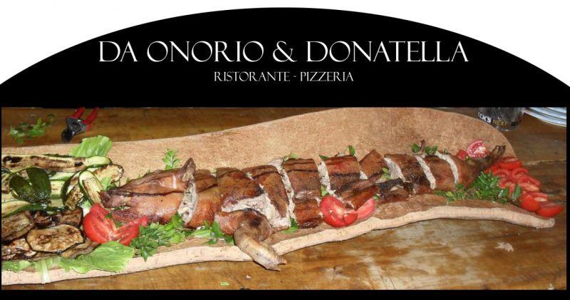 Da Onorio e Donatella - offerta ristorante che serve maialetto sardo cotto allo spiedo nel camino